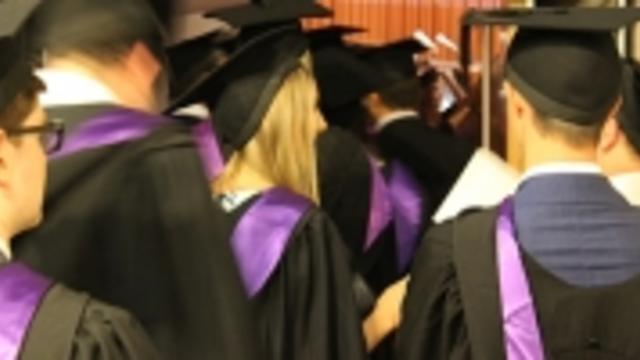 Backs of graduates with purple sash and mortboards