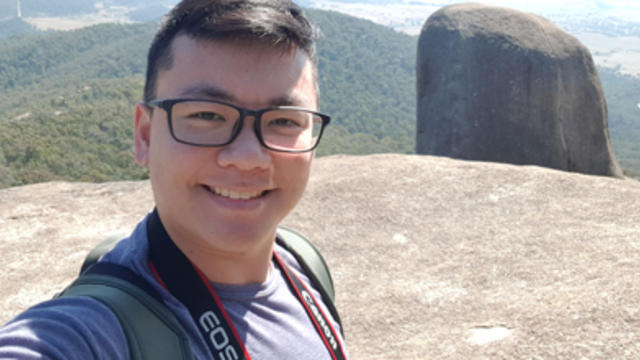 Joshua Ling smiling in front of beautiful landscape