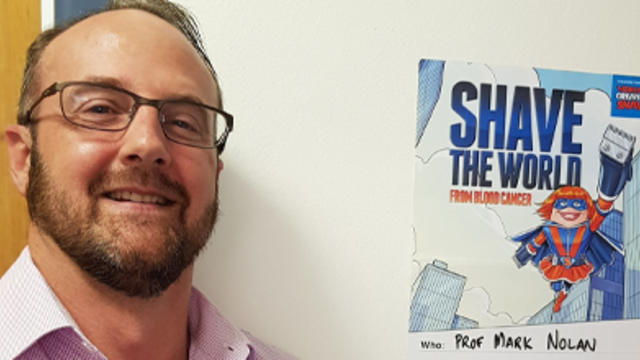Professor Mark Nolan next to a poster about the Worlds Greatest Shave