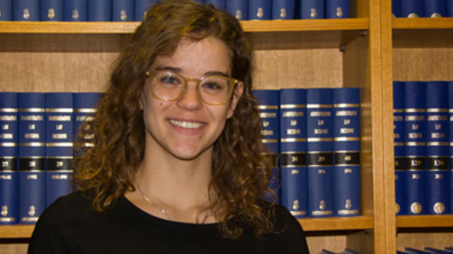 Georgie Juszczyk smiling in the Phillipa Weeks Law Library