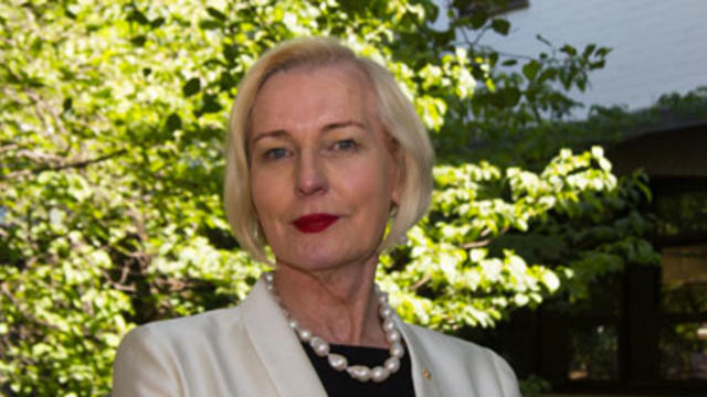 Catherine McGregor AM wears a white jacket and stands in front of trees outside the ANU College of Law