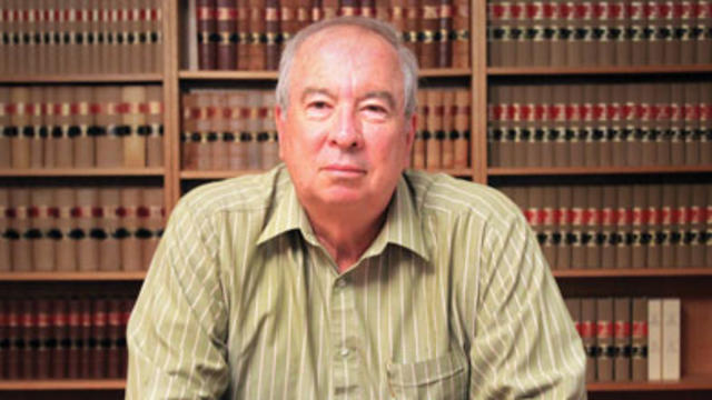 Professor Clive Williams sits at a desk, behind him are law journals