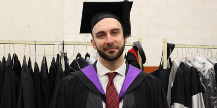 Image shows graduation student speaker Max Henshaw in his graduation robe