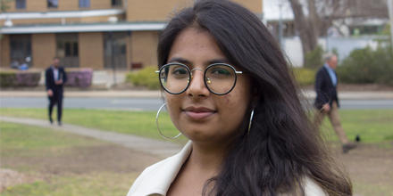 Anjali Goyal smiling in front of the ANU Law building