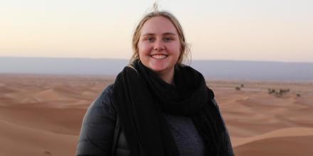 Samantha sitting on a desert sand dune