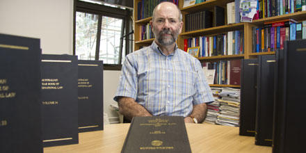 Professor Donald Rothwell is flanked by two rows of Australian Year Book of International Law