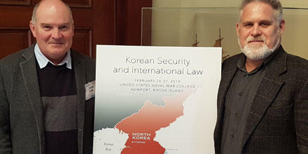 Photo shows David Letts (left) and Kevin Heller with a Korean Peninsula sign at the US Naval College