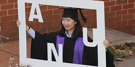 Graduation July 2017 Student holds ANU Frame