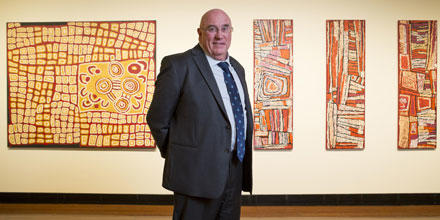 Craig Edwards stands in front of  four paintings by Indigenous artists