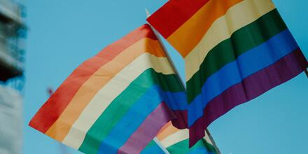 Pride flags in the wind, on a blue sky backdrop.