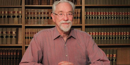 Professor David Hambly is seated at a desk, in front of law journals