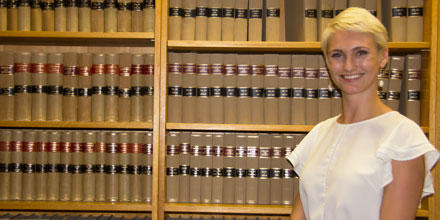 Image shows Kirsten Storey standing in front of law journals at ANU