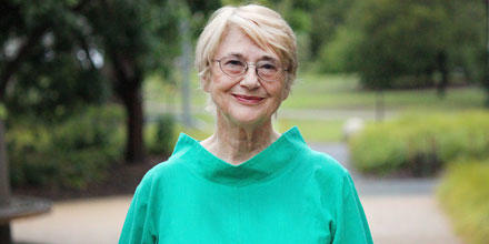 Professor Margaret Thornton stands outside and is wearing a green top
