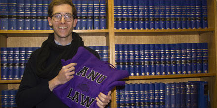 Nicholas Horton stands in front of a book case and holds a purple hoodie sweater featuring the words ANU Law