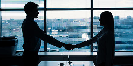 Two people shacking hands in corporate setting