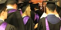 Backs of graduates with purple sash and mortboards