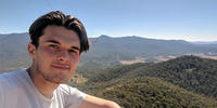Joe Dean smiling behind him beautiful green landscape