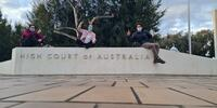The winning ANU team members Tom Dunbabin, Madeleine McGregor, and Benjamin Durkin, sitting on top of the High Court of Australia sign.