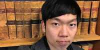 Image shows Ben Ye in front of Victorian Law Report volumes