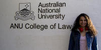JD student Hansika Chopra stands beside a sign saying ANU College of Law
