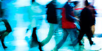 Image is deliberately blurred and shows people walking