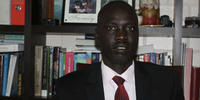 Image shows ANU Juris Doctor student Elijah Buol in front of a book case