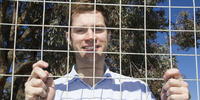 Danny Philippa stands behind a wire fence on campus