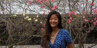 Student Gina Zheng stands in front of a blooming tree