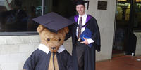 Marcus on graduation day sitting next to a huge stuffed bear