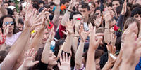 image shows people in a crowd raising their hands, some are carrying roses
